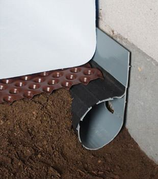 Closeup of a crawl space drainage system installed in Lanigan