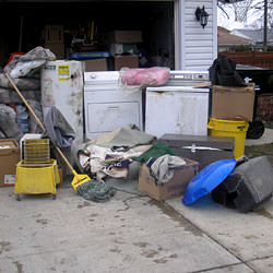 Soaked, wet personal items sitting in a driveway, including a washer and dryer in Meadow Lake.