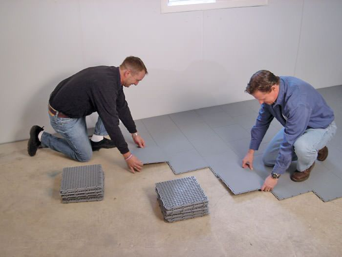 ... Contractors Installing Basement Subfloor Tiles And Matting On A  Concrete Basement Floor In Lloydminster, Saskatchewan